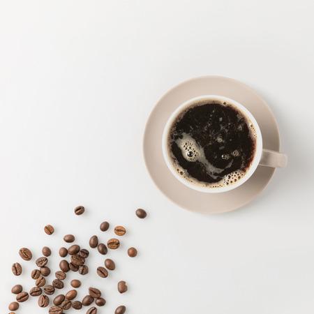 Foto de top view of coffee cup with beans on white surface - Imagen libre de derechos