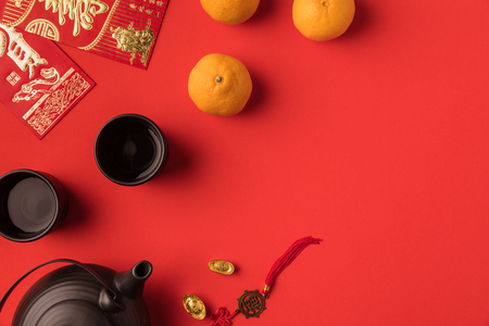 Photo pour top view of oriental decorations, greeting cards with calligraphy and ceramic tea set isolated on red - image libre de droit