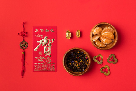 Foto de top view of chinese greeting card with calligraphy, oriental decorations and tangerines isolated on red - Imagen libre de derechos