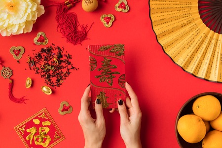 Foto de cropped shot of female hands holding greeting card with calligraphy and tangerines with oriental decorations isolated on red - Imagen libre de derechos