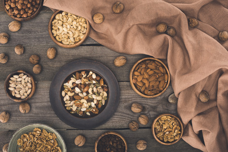Photo for top view of various nuts in bowls and fabric on wooden table - Royalty Free Image