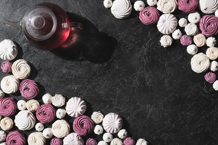 Foto de top view of white and berry marshmallows with teapot on black tabletop with copy space - Imagen libre de derechos