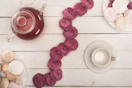 Foto de top view of white and berry marshmallows, cup and tea on white wooden tabletop   - Imagen libre de derechos