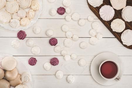 Foto de top view of white and berry marshmallows and tea on white wooden tabletop  - Imagen libre de derechos