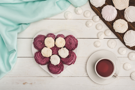 Foto de white and berry marshmallows and tea on white wooden tabletop with turquoise tablecloth - Imagen libre de derechos