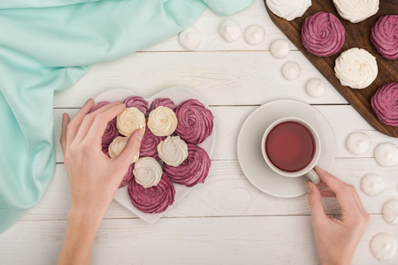 Foto de cropped view of woman with heart shaped white and berry marshmallows and tea on white wooden tabletop with turquoise tablecloth - Imagen libre de derechos