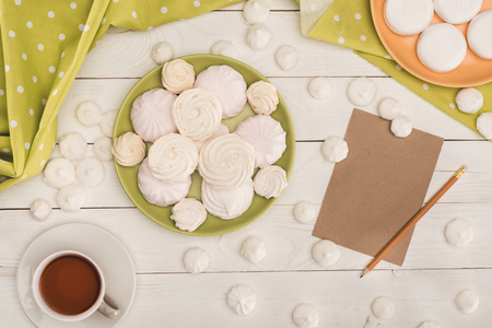 Foto de top view of white marshmallows, tea and card on white wooden tabletop with green tablecloth - Imagen libre de derechos