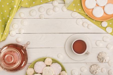 Foto de white marshmallows and tea on white wooden tabletop with green tablecloth - Imagen libre de derechos