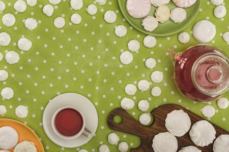 Foto de white marshmallows and tea on green polka dot tablecloth - Imagen libre de derechos