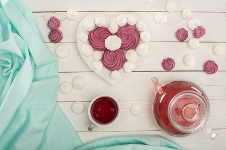 Foto de heart shaped marshmallows and tea on white wooden tabletop with turquoise tablecloth - Imagen libre de derechos