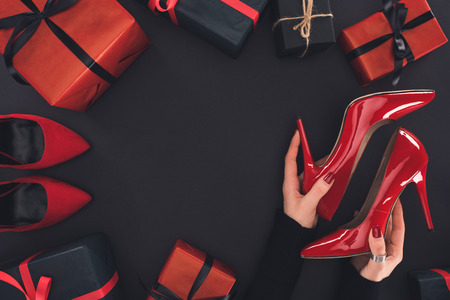 Foto de cropped view of woman holding red heels, isolated on black with presents and tags - Imagen libre de derechos