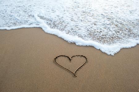 Foto de heart shape sign erasing by ocean wave on sandy beach - Imagen libre de derechos