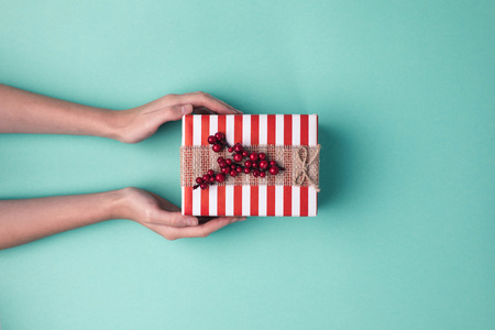 Foto de cropped shot of female hands holding wrapped christmas gift with ribbon on blue surface - Imagen libre de derechos