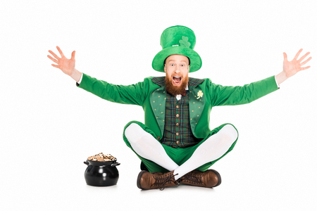 Foto de excited leprechaun gesturing and sitting at pot of gold - Imagen libre de derechos