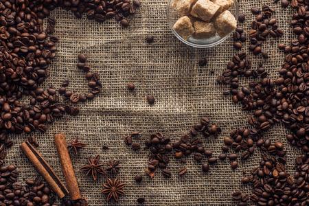 Foto de roasted coffee beans with cinnamon sticks, star anise and brown sugar in glass bowl - Imagen libre de derechos