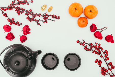 Foto de top view of chinese new year composition with tea and branches of berries - Imagen libre de derechos