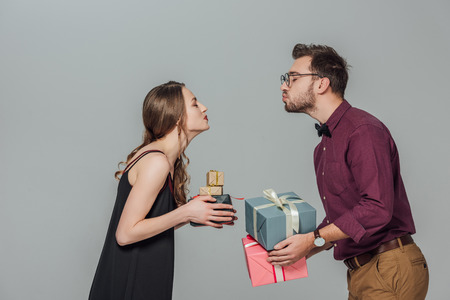 Foto de side view of happy young couple holding gift boxes and able to kiss - Imagen libre de derechos