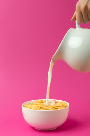 Photo for partial view of person pouring fresh healthy milk from jug into bowl with corn flakes - Royalty Free Image
