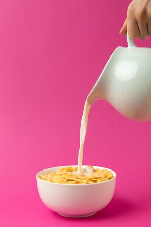 Foto de partial view of person pouring fresh healthy milk from jug into bowl with corn flakes - Imagen libre de derechos