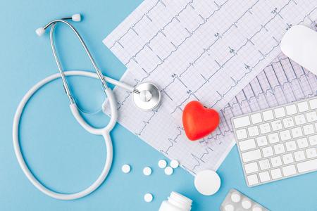 Foto de stethoscope, paper with cardiogram, scattered pills, red heart and keyboard - Imagen libre de derechos