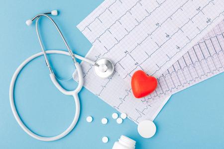 Foto de stethoscope, paper with cardiogram, scattered pills and red heart - Imagen libre de derechos