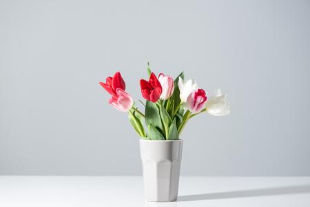 Foto de blooming white, pink and red tulips in vase on grey - Imagen libre de derechos