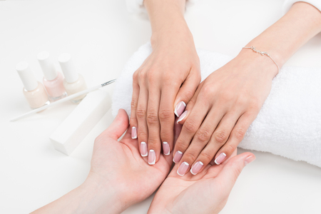 Photo for cropped shot of manicurist holding female hands with beautiful french manicure - Royalty Free Image