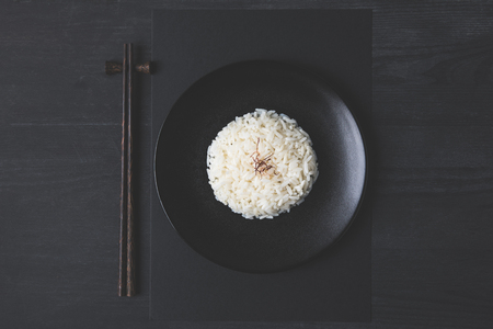 Photo for top view of tasty rice and chopsticks on black table - Royalty Free Image
