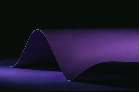 Foto de warping purple paper on purple surface on black - Imagen libre de derechos