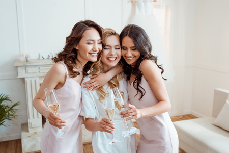 Photo for bride with bridesmaids embracing and toasting - Royalty Free Image