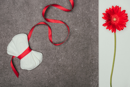 Photo pour arranged menstrual pads with ribbon and red flower on grey surface - image libre de droit