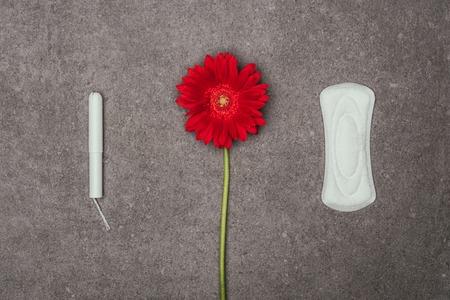 Photo pour top view of arrangement of red flower, menstrual pad and tampon - image libre de droit