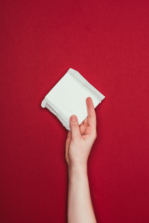 Photo pour woman holding menstrual pad in hand isolated on red - image libre de droit