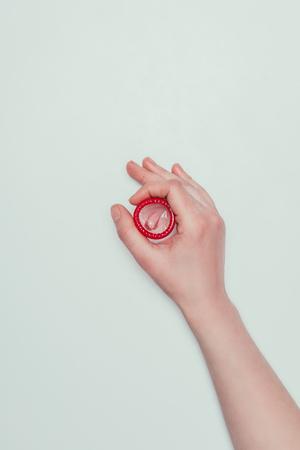 Foto de partial view of woman holding opened condom in hand - Imagen libre de derechos