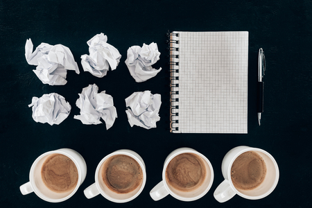 Photo pour top view of blank notebook with crumpled papers and cups of coffee in row isolated on black - image libre de droit