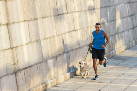 Photo pour sportsman running with dog - image libre de droit