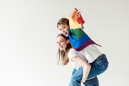 Photo for Woman giving piggyback to girlfriend with flag - Royalty Free Image