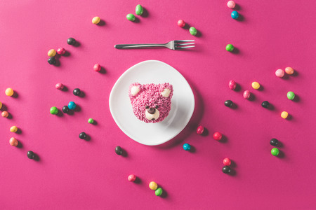 Photo for top view of dessert in shape of bear head on plate on pink surface - Royalty Free Image