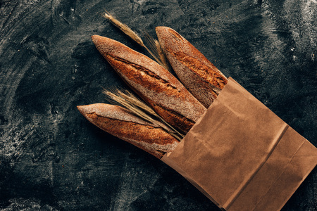 Foto de top view of arranged french baguettes in paper bag and wheat on dark tabletop with flour - Imagen libre de derechos