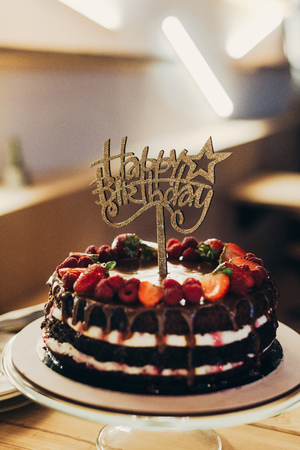 Photo pour Happy Birthday sign on chocolate cake with fruits - image libre de droit