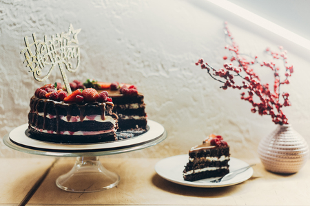 Foto de Cake with Happy Birthday sign on cake stand and piece of cake on a table - Imagen libre de derechos