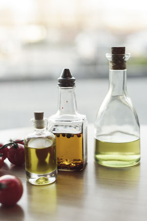 Photo pour close up view of various types of oil in bottles and fresh cherry tomatoes - image libre de droit