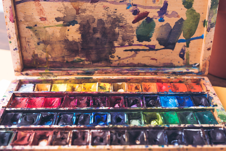 Photo for close-up view of watercolor paints in messy container with brush strokes and spots - Royalty Free Image