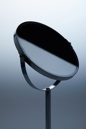 Photo pour close-up shot of cosmetic mirror with stand on grey - image libre de droit