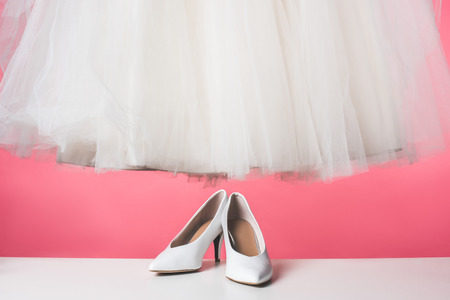 Photo pour pair of white shoes and wedding dress isolated on pink - image libre de droit