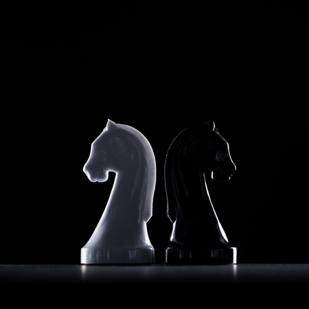 Foto de silhouettes of white and black chess knights isolated on black, business concept - Imagen libre de derechos