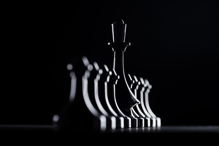 Foto de silhouettes of chess pawns and queen isolated on black, business concept - Imagen libre de derechos