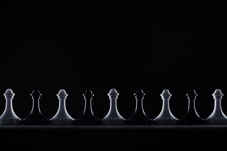 Foto de silhouettes of black and white chess pawns isolated on black, business concept - Imagen libre de derechos