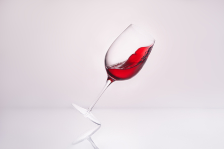 Foto de close-up shot of inclined wineglass with splashing red wine on reflective surface and on white - Imagen libre de derechos