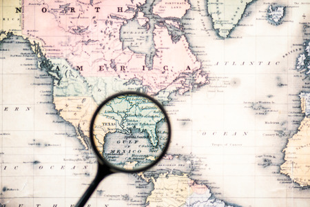 Photo for top view of magnifying glass on world map over gulf mexico - Royalty Free Image